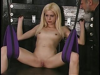 Small titted blonde in swing plays with her twat